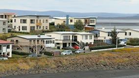 Строить и припаркованные автомобили в окраинах малых исландских городка, реки и гор в предпосылке сток-видео