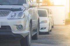 Строка автомобилей припарковала на конкретном поле на месте для стоянки автомобиля с предпосылкой солнечного света Стоковые Фотографии RF