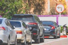 Строка автомобилей припарковала на конкретном поле на месте для стоянки автомобиля с солнечным светом на заднем плане Стоковая Фотография RF