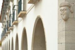 Строка аркад, расположенная на квадрате Republica, со статуей представляя голову человека нося усик на правильной стороне, стоковые изображения rf