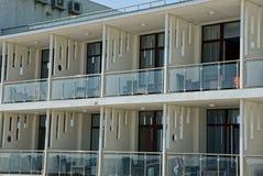 Строка балконов белизны открытых стеклянных с мебелью на стене гостиницы стоковые изображения
