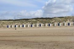 Строка белых пляжных домиков с желтыми и голубыми дверями перед дюнами с травой пляжа в cadzand, Голландии Стоковые Изображения RF