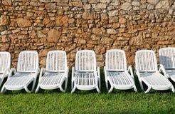 Строка белых пластичных loungers солнца Стоковые Изображения RF