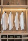 Строка белых рубашек вися на рельсе Стоковое Фото
