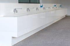 Строка водопроводного крана и раковины в школе Стоковые Изображения