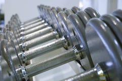 Строка гантелей для поднятия тяжестей в спортзале Стоковые Фото