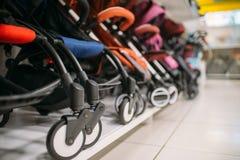 Строка детских сидячих колясок на полке в магазине, никто стоковая фотография