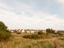 Строка домов на крае побережья за полем через небо пути и Стоковые Фото