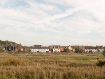 Строка домов на крае побережья за полем через небо пути и Стоковая Фотография