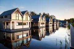 Строка домов с окнами зеркала на озере Стоковое фото RF