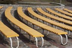 Строка желтых деревянных мест на фото трибуны зрителя Стоковые Изображения RF