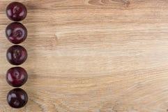 Строка зрелых слив от деревянного стола левой стороны Стоковое Фото