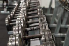 Строка используемых гантелей металла на шкафе в спортзале Оборудование спорта и фитнеса Стоковое Изображение