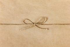 Строка или шпагат связанные в смычке на бумаге kraft стоковые фото