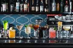Строка коктейлей различного colourfull спиртных на столе бара Стекла differen формы стоковое фото rf