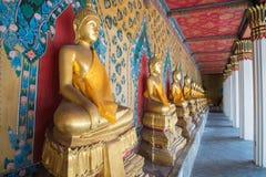 Строка красивого сидя Buddhas на виске в Бангкоке, Таиланде стоковое фото rf