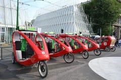 Строка красных швейцарских современных trishaws припаркованных в квадрате Castello Sforzesco в Милане стоковое изображение