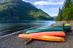 Строка красочных каяков лежа на береге полумесяца озера стоковые фотографии rf