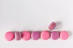 Строка красочных французских macarons на белой предпосылке Взгляд сверху Стоковые Изображения RF