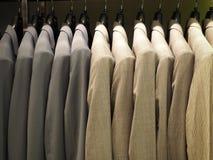 Строка мужских курток костюма в магазине одеяния стоковые фотографии rf