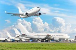 Строка пассажирского самолета, самолета припарковала на обслуживании перед отклонением на авиапорте, другие плоские нажимают наза стоковая фотография