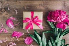 Строка пионов и подарочной коробки на деревянной предпосылке с космосом для сообщения ` S женщин или ` s матери предпосылка дня В Стоковое Изображение RF