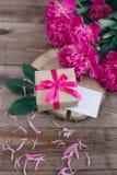 Строка пионов и подарочной коробки на деревянной предпосылке с космосом для сообщения ` S женщин или ` s матери предпосылка дня В Стоковое фото RF