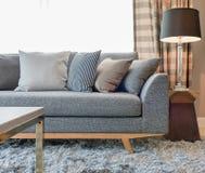 Строка подушек на серой софе с черной лампой в живущей комнате Стоковая Фотография RF