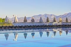 Строка пустых sunbeds бассейном и морем в утре на зоре Удобная гостиница высотного здания Стоковые Изображения