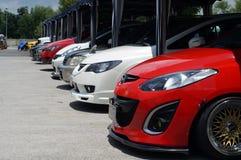Строка различных цвета и модели автомобиля припарковала в дворе выставки автомобиля Стоковая Фотография