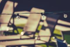 Строка светов на палубе бассейна с предпосылкой Loungers Солнця Стоковые Фото