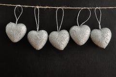 Строка серебряных сердец вися на веревочке Стоковые Изображения RF