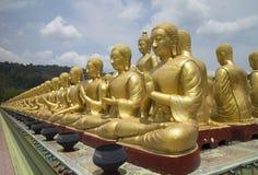 Строка статуи Будды статуй ученика окружающей большой стоковые фото