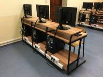 Строка стульев, компьютеров и мониторов на таблице в пустом классе Стоковые Фото