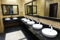 Строка тазов мытья с зеркалами в общественном туалете Стоковое Фото