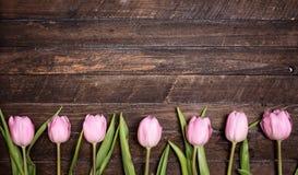 Строка тюльпанов на деревянной предпосылке с космосом для сообщения Mothe Стоковые Изображения RF