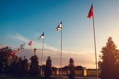 Строка флагов летания наций на предпосылке неба захода солнца флаги стран различные Стоковые Фотографии RF