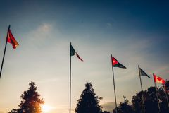 Строка флагов наций на предпосылке неба захода солнца флаги стран различные Соединение наций Мир в мире Стоковое Изображение