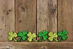 Строка shamrocks дня St Patricks против старой древесины Стоковая Фотография RF
