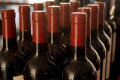 Строки бутылок вина загерметизированных в красном цвете Стоковая Фотография