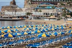 Строки голубых sunbeds с голубыми и желтыми парасолями на пляже Playa de Пуэрто-Рико на Канарских островах Стоковое Изображение RF