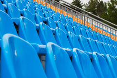 Строки голубых и оранжевых стульев на футбольном стадионе Стоковые Изображения