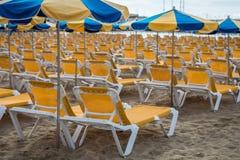 Строки желтых sunbeds с голубыми и желтыми парасолями на пляже Playa de Пуэрто-Рико на Канарских островах Стоковые Изображения