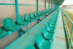 Строки мест в пустом стадионе зеленый цвет усаживает стадион Стоковое Изображение