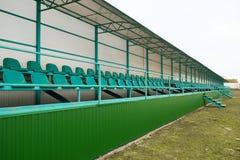 Строки мест в пустом стадионе зеленый цвет усаживает стадион Стоковые Фото
