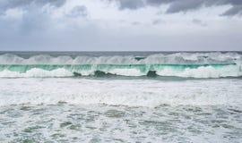 2 строки моря бирюзы развевают, пена воды и драматические облака Стоковое Изображение