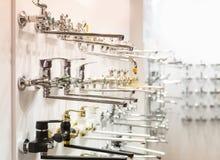 Строки новых faucets для ванной комнаты в трубопроводе ходят по магазинам стоковое изображение rf
