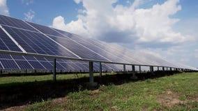 Строки панелей солнечных батарей на зеленой траве против голубого неба с облаками Станция солнечной энергии в поле акции видеоматериалы
