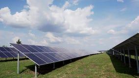Строки панелей солнечных батарей на зеленом поле против голубого неба с облаками Станция солнечной энергии сток-видео