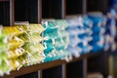 Строки покрашенных свечей обедающего воска на дисплее в магазине в полках стоковая фотография rf